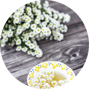 Chamomile flowers and tea on a weathered wooden table